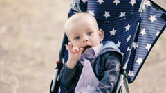 Little boy sitting in baby carriage - stock footage