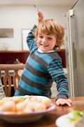 Young boy with fork raised about to stab potato Stock Photos