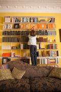 Young boy reaching up to get a book from a bookcase Stock Photos