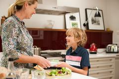 Son helping to carry napkins for mother, in preparation for meal Stock Photos