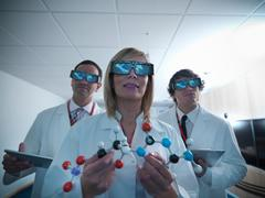 Three scientists in lab coats wearing 3D glasses and holding molecular model Stock Photos