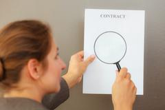 Business woman with contract and loupe Stock Photos