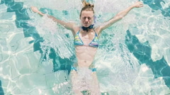 SLOW MOTION: Woman jumping and swimming in the pool underwater Stock Footage