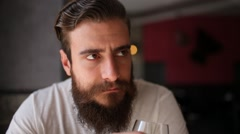 Young man with a beard listen to the guest, then drink a glass of white wine Stock Footage