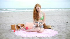 Beach bikini female making reading journal USA - stock footage