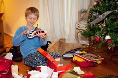 Boy opening Christmas presents Stock Photos