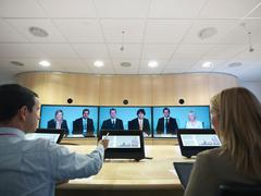 Businesspeople in meeting room using screens in video conference Kuvituskuvat