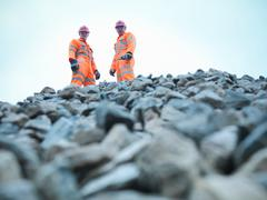 Portrait of quarryman and assistant standing on stockpile of quarried stone - stock photo