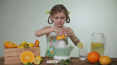 Girl squeezes out juice of a grapefruit - stock footage