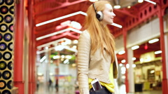 Caucasian female with headphones in mall USA Stock Footage