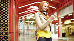 Female in mall outside record shop using internet USA - stock footage