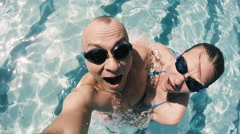 Young man and woman in swimming goggles selfie in the pool Stock Footage