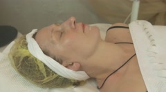 Stock Video Footage of Adult woman lie in beauty saloon under white blanket. Anti aging slincare