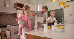 Family of Four Standing and Having Breakfast in Kitchen Stock Footage