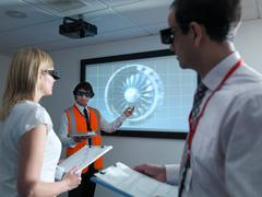 Engineers and apprentice in 3D glasses with clipboards in front of  engine on 3D Stock Photos