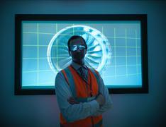 Portrait of engineer standing in front of engine part on 3D screen Kuvituskuvat