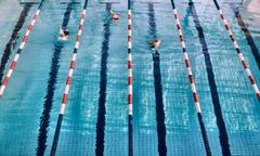 Swimmers in lanes of swimming pool Stock Photos