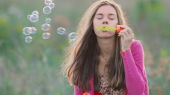 Young woman sitting on meadow grass blowing soap bubbles Stock Footage