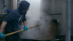 4K Worker in a brewery removing mash from the bottom of a machine Stock Footage