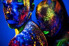people are colored fluorescent powder. a pair of lovers dancing at a disco. - stock photo