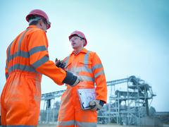 Low angle view of quarryman advising apprentice in front of stockpile quarry - stock photo