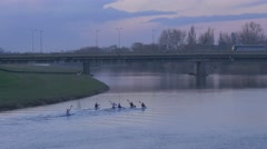 Sportsmen Paddle a Canoes Buses on Car Bridge Through River City on River Bank Stock Footage