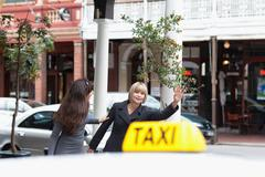 Women hailing taxi cab in city Stock Photos