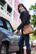 Woman unlocking car on city street Stock Photos