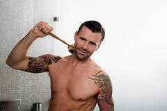 Man scrubbing his back in shower Stock Photos