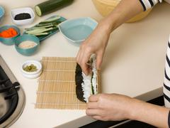 Woman rolling sushi at table Stock Photos