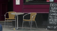 A table and two chairs in front of the Footlights Bar and Grill, Edinburgh - stock footage