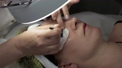 Cosmetologist make permanent dyeing of eyelashes to woman in beauty saloon Stock Footage