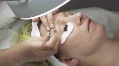 Cosmetologist pull out eyebrow, while dyeing eyelashes to woman in beauty saloon - stock footage