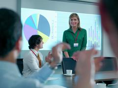 Businesswoman congratulated by colleagues in conference room for smart board Stock Photos