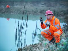 Stock Photo of Ecologist taking soil sample from bank next to water on quarry site
