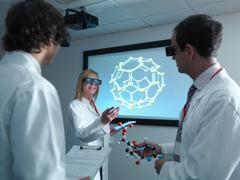 Scientists and apprentice in 3D glasses in meeting in front of molecular model Stock Photos