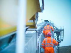 Workmen in reflective clothing climbing steps of screening conveyor at quarry - stock photo