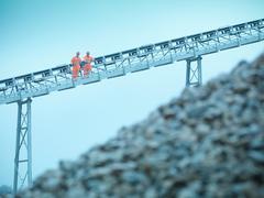 Quarrymen standing on stockpile conveyor at stone quarry - stock photo
