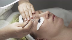 Cosmetologist corrects eyebrow, while dyeing eyelashes to woman in beauty saloon - stock footage