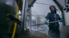 4K Worker in a brewery removing mash from the bottom of a machine - stock footage