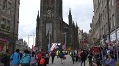 People walking in front of an old church on Royal Mile, Edinburgh Stock Footage