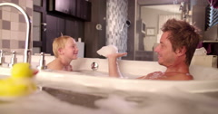 Modern Dad Plays with Son in Bubble Bath at Home Stock Footage