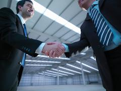Low angle view of property managers shaking hands in finished factory building - stock photo