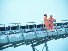 Workmen in reflective clothing on steps of screening conveyor at quarry Stock Photos