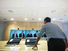 Businessman standing in meeting room addressing colleagues on  video conference Stock Photos