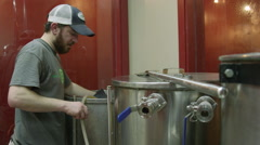 Craft Beer Brewer Working Over Large Brew Kettle at Brewery Stock Footage