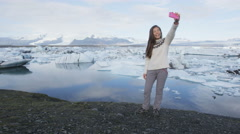 Girl taking selfie photo with phone in Iceland - Jokulsarlon glacial lagoon Stock Footage