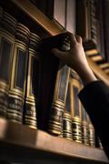 Hand pulling book from bookshelf Stock Photos