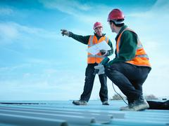 Building foreman holding plans and directing apprentice on factory roof Stock Photos