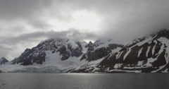 Passing arctic glacier and snowy mountains from ship Stock Footage